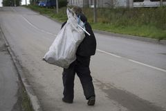 Бездомный человек идет с сумкой стоковое фото