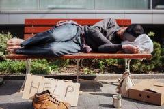 Бездомный человек лежит на стенде и спать Hee утомлено и вымотано Сумка с веществом под его головой стоковая фотография rf