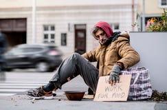 Бездомный человек попрошайки сидя outdoors в городе прося пожертвование денег стоковые фото
