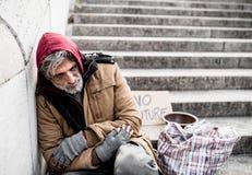 Бездомный человек попрошайки сидя outdoors в городе прося пожертвование денег стоковая фотография