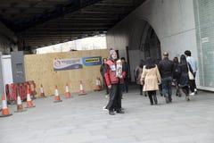 Бездомный человек продавая экземпляры большого вопроса Стоковое Фото