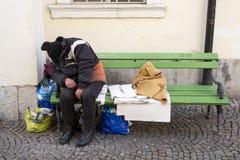 Бездомный человек спать на стенде стоковые изображения