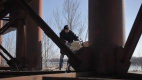 Бездомный человек wallking нажимающ тележку под мостом видеоматериал