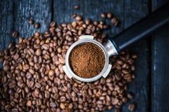 Бездонный фильтр с фасолями молотилки на деревянной черной таблице зажаренный в духовке кофе фасолей Извлечение кофе эспрессо Под стоковое фото rf