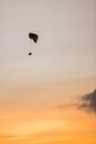 Безмятежность парашюта нисходящая в золотом заходе солнца Стоковое Фото