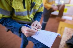 Безопасность инспектора шахтера конструкции проводя проверяя на анализе опасностей работы на горячем разрешении на работу перед з стоковые фотографии rf