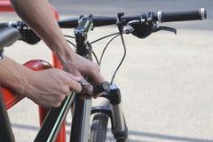 Безопасность и переход - близкие вверх замка велосипеда крепления человека на автостоянке улицы Стоковое Изображение RF
