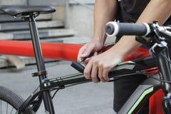 Безопасность и переход - близкие вверх замка велосипеда крепления человека на автостоянке улицы Стоковые Изображения