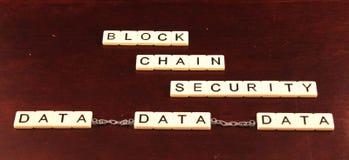 Безопасность цепи блока сказала по буквам вне в плитках на предпосылке вишни деревянной при данные прикованные совместно undernea стоковое изображение