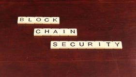Безопасность цепи блока сказала по буквам вне в плитках на предпосылке древесины вишни стоковая фотография