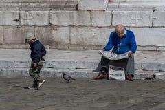 Безразличное чтение старика рядом с мальчиком стоковое фото
