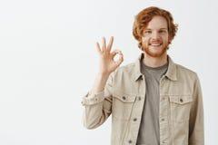 Безупречная работа, гордая нашей команды Портрет удовлетворенного симпатичного человека дружелюбного и беспечального redhead боро стоковая фотография rf