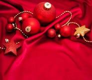 Безделушки рождества на красном шелке Стоковые Изображения