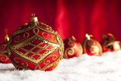 Безделушки рождества на снеге и красной предпосылке Стоковые Фотографии RF