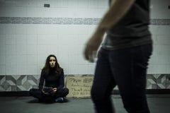 Бездомная женщина попрошайки прося пожертвование денег с пожалуйста помогает Стоковое фото RF