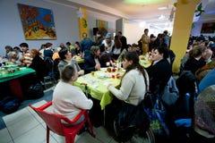 Бездомные и нездоровые люди сидят вокруг таблиц с едой на обедающем призрения рождества для бездомные как Стоковые Фото