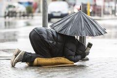Бездомный попрошайка с зонтиком в дожде Стоковые Изображения RF