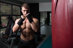 Без рубашки мышечный боксер с грушей в спортзале Стоковая Фотография