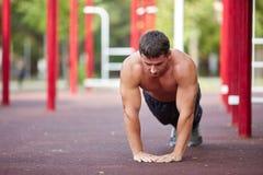 Без рубашки мышечный делать молодого человека нажим-поднимает на предпосылке outdoors Концепция тренировки скопируйте космос стоковое фото