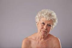 Без рубашки пожилая женщина смотря унылый Стоковое Фото