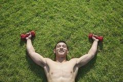 Без рубашки, усмехающся, мышечный человек лежа в траве с гантелями в Пекине, осматривает сверху Стоковые Фото