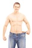 Без рубашки усмехаясь мужчина показывая его потерянный вес путем установка на стоковые изображения rf