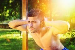 Без рубашки человек делая сидения на корточках outdoors на солнечный летний день Стоковые Изображения RF