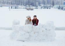 Без сокращений взгляд жизнерадостных пар стоя за стеной и смеяться над снега Положение деревни зимы Стоковые Фотографии RF