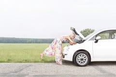 Без сокращений взгляд со стороны женщины рассматривая сломанный вниз с автомобиля на проселочной дороге Стоковая Фотография