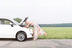 Без сокращений взгляд со стороны женщины рассматривая сломанный вниз с автомобиля на проселочной дороге Стоковая Фотография RF