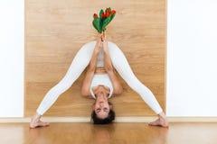 Без сокращений вид спереди sporty молодой женщины в йоге белого костюма практикуя делая стоять колеблет переднее представление за Стоковое Фото