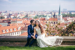 Без сокращений горизонтальное фото очаровательных пар новобрачных на предпосылке панорамы Праги Groom Стоковая Фотография