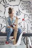 Без сокращений девушки при скейтборд сидя на таблице исследования дома Стоковое Изображение