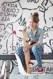 Без сокращений девушки при скейтборд сидя на таблице исследования дома Стоковая Фотография RF