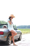 Без сокращений женщины используя сотовый телефон пока полагающся на автомобиле с откидным верхом на сельской местности Стоковое Фото
