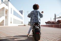 Без сокращений заднее изображение взгляда курчавой девушки едет на мотоцилк Стоковое Фото