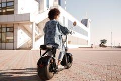 Без сокращений заднее изображение взгляда маленькой девочки едет на мотоцилк Стоковое Изображение RF