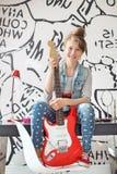 Без сокращений портрет девушки при электрическая гитара сидя на исследовании ставит на обсуждение дома Стоковое Фото
