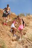 Без сокращений портрет компании усмехаясь молодые люди идя вниз от холма на естественной запачканной предпосылке Стоковое Изображение