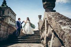 Без сокращений портрет свадьбы прелестных пар новобрачных идя вниз с старых strais замка Groom помогает его Стоковое Изображение RF