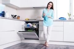 Без сокращений портрет счастливой молодой домохозяйки в белых джинсах и рубашке бирюзы в белой кухне стоя с полотенцем в h стоковое фото