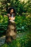 Без сокращений портрет шикарной африканской девушки с зеленым составом в стильной одежде наслаждаясь природой в Стоковые Изображения RF