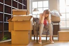 Без сокращений разочарованной женщины сидя картонными коробками в новом доме стоковое изображение