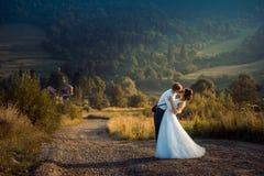Без сокращений свадьба сняла прелестных новобрачных мягко целуя на дороге на предпосылке гор во время Стоковое Изображение RF