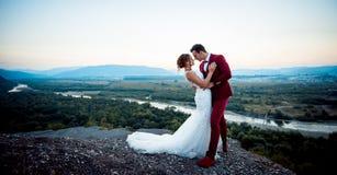 Без сокращений свадьба сняла прелестных новобрачных обнимая на adge гор на предпосылке  Стоковая Фотография RF