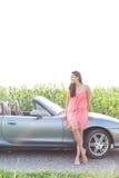 Без сокращений склонности женщины на автомобиле с откидным верхом против ясного неба Стоковое фото RF