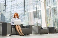 Без сокращений средн-постаретой коммерсантки используя компьтер-книжку на лобби офиса Стоковые Фото