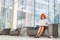 Без сокращений средн-постаретой коммерсантки используя компьтер-книжку на лобби офиса Стоковое фото RF