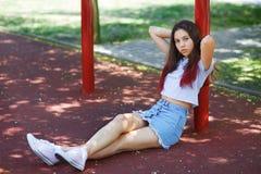 Без сокращений фото красивого девочка-подростка в вскользь одеждах и розовых gumshoes сидя на земле спортивной площадки Стоковое Изображение