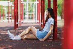Без сокращений фото красивого девочка-подростка в вскользь одеждах и розовых gumshoes сидя на земле спортивной площадки Стоковые Фото